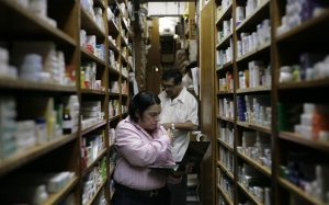 Pharmacy employees check medicine supplies at medicine for sale in a drugstore in Caracas